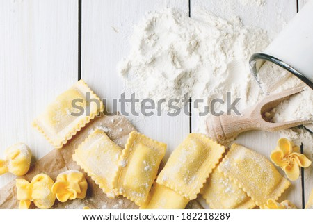 Top view on homemade pasta ravioli and perle on white wooden table with vintage mug of flour. See series - stock photo