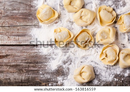 Top view on homemade pasta ravioli over wooden table with flour - stock photo