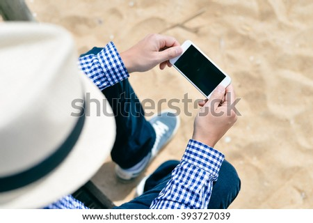 Top view on male using mobile phone on tropical beach background. Hand hold mockup black screen display - stock photo