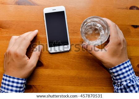 Top view on man working on mobile phone, hands and glass of water on wooden desk background. - stock photo