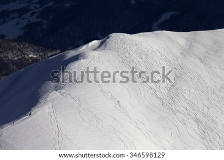 Top view on off piste slope with snowboarders and skiers at evening. Caucasus Mountains, Georgia, ski resort Gudauri. - stock photo