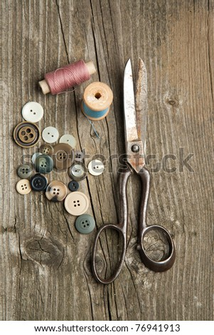 Top view on old scissors, cottons and buttons on wooden desk - stock photo
