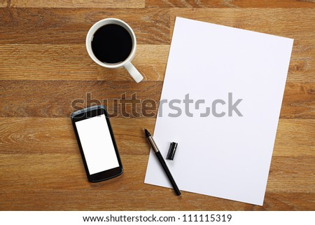 Top view on paper, smartphone, pen and cup of coffee on wooden office desk. - stock photo