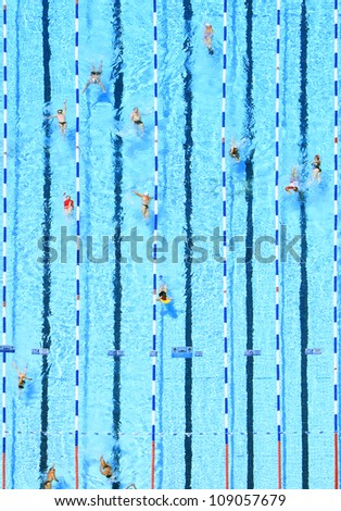 Top view on pool with blue water and swimming people - stock photo