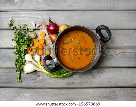 Top view on pot of tomato soup and fresh vegetables on old wooden table - stock photo