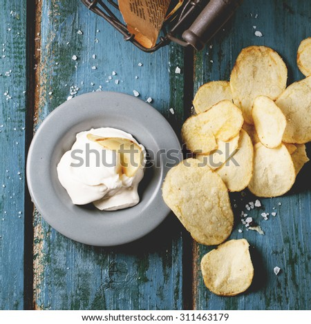Top view on potato chips with plate of sause and sea salt over blue wooden table. Square image - stock photo