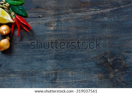 Top view on red hot chili peppers, onions, lemon and spices over dark wooden background with copyspace.   - stock photo