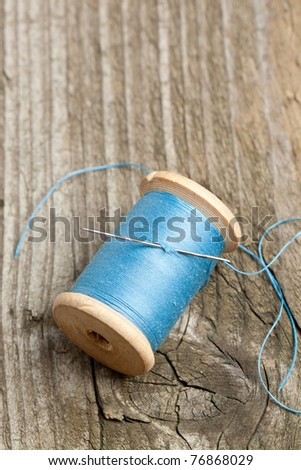 Top view on spool of blue thread and needle on old wooden table - stock photo