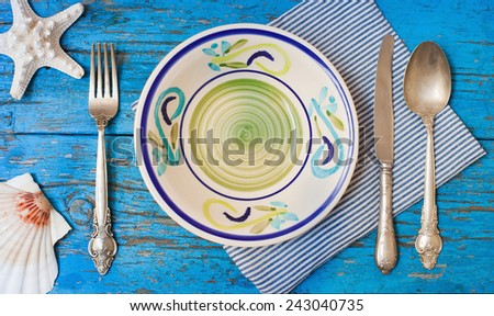 Top view on table setting with vintage silverware with plate on blue wooden table in sea stile  - stock photo