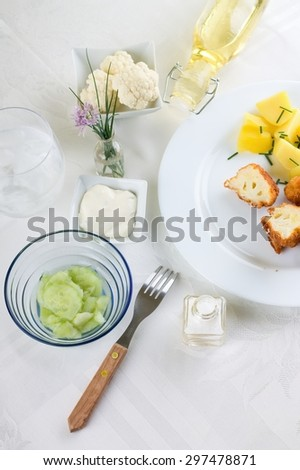 Top view on table with white cloth and fork, glass with salt, glass with oil, bowl with cucumber salad, vegetable, flower chive and dip around plate with breaded cauliflower and potatoes. - stock photo
