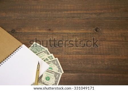 Top View On The Rustic Rough Brown Wood Table With USA Dollar Cash, Opened Pocketbook With White Page And Gold Fountain Pen, Business Or Home Finance Concept  And Background With Copy Space - stock photo