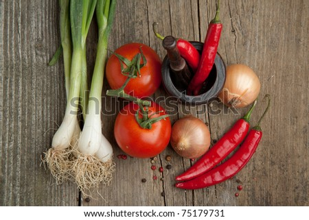 Top view on tomato, onions and red hot chili peppers in old mortar on old wooden table - stock photo