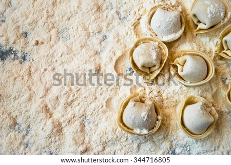 Top view on uncooked meat dumplings lies on right side of the table - stock photo