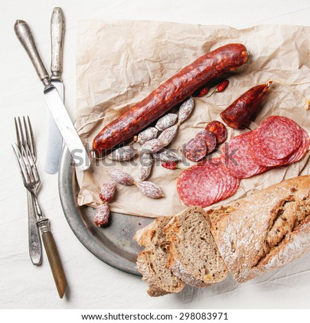 Top view on vintage tray with set of salami sausages with fresh bread and red hot chili peppers served with vintage tableware on white tablecloth. Top view. Square image - stock photo