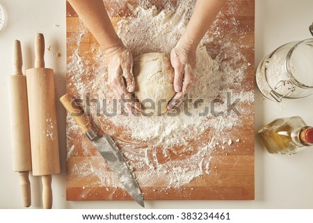 Top view on white table with isolated wooden board with knife, two rolling pins, bottle olive oil, transparent jar with flour Woman hands hold prepared dough for pasta or dumplings - stock photo