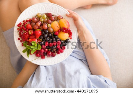 Top view on woman sitting cozy on the couch and enjoying delicious summer fruit and berries. Girl holding white plate with apricots, raspberries, strawberries, blackcurrant, blueberries on her knees - stock photo
