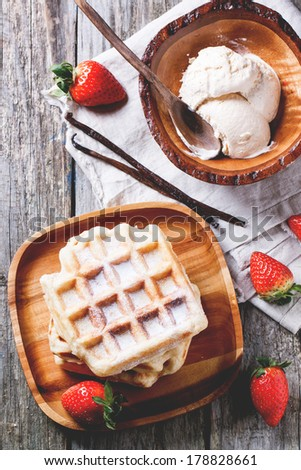 Top view on wooden plate with fresh belgian waffles and bowl of ice cream, served with strawberries and vanilla sticks over wooden table. See series - stock photo