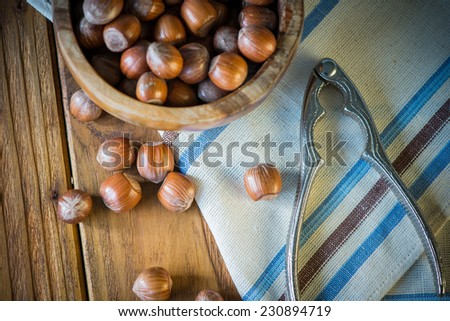 top view over hazelnuts in bowl and nut cracker on cloth - stock photo
