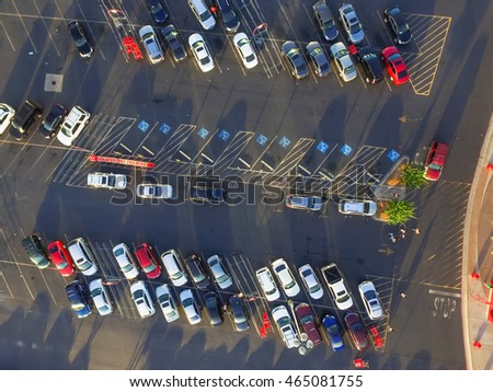 Top view parking lots with rows of parked car, shopping carts, road sign for disabled drivers at a supermarket in Houston, Texas, USA at sunset. Urban infrastructure and transportation concept