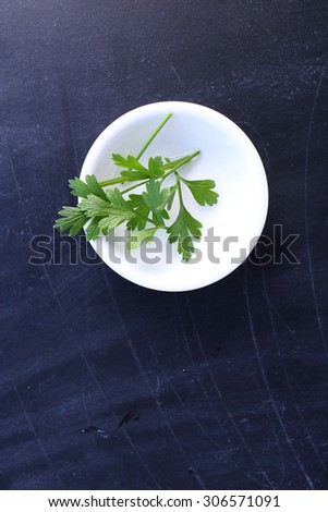 Top view parsley in bowl on black background - stock photo
