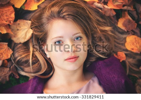 Top view photo from a beautiful young women lying between colorful autumn leafs - stock photo