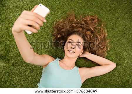 Top view photo of beautiful young woman lying on green grass. Woman cheerfully smiling, making selfie photo with mobile phone - stock photo