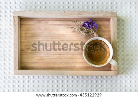 Top view photo of coffee and spring flowers on wooden tray, Espresso coffee in wooden tray place on Table in garden, Espresso coffee with wooden tray and wooden spoon on white table in garden - stock photo