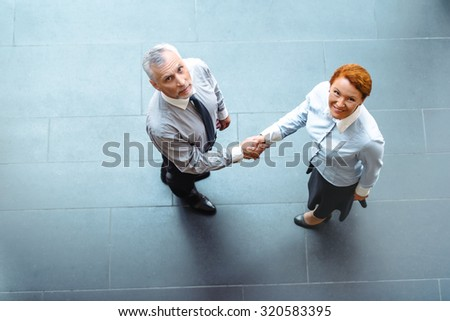 Top view photo of creative business people. Business people smiling and shaking hands while meeting - stock photo