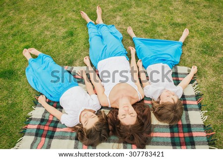 Top view photo of family on relaxing with closed eyes on blanket during the day on picnic. Daughters have the same clothes as mother - stock photo