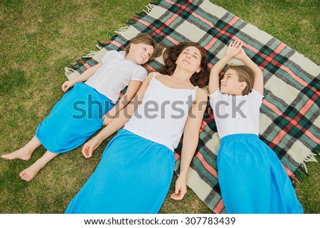 Top view photo of family relaxing on blanket on the nature. Daughters have the same clothes as mother and look at the mother - stock photo