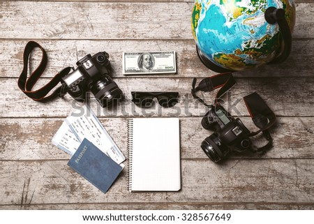 Top view photo of globe, two professional cameras, notebook, passport, tickets, money and sunglasses. Objects are on light colored wooden floor - stock photo