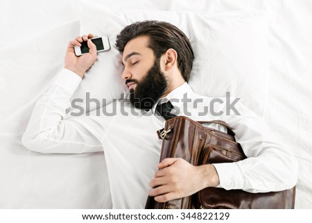 Top view photo of handsome sleepy dark haired businessman with beard sleeping in white bed. Man wearing shirt and tie. Businessman holding leather bag and mobile phone - stock photo