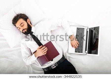 Top view photo of handsome sleepy dark haired businessman with beard sleeping in white bed. Man wearing shirt and tie. Businessman with notebook lying near laptop