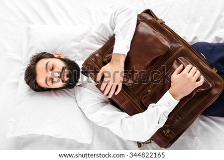 Top view photo of handsome sleepy dark haired businessman with beard sleeping in white bed. Man wearing shirt and tie, and holding leather bag