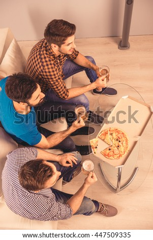 top-view photo of happy cheerful men  holding glass of beer and watching tv - stock photo