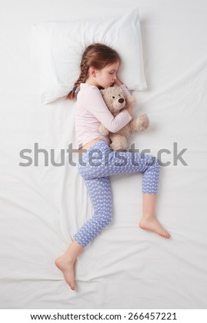 Top view photo of little cute girl sleeping on white bed and hugging teddy bear. Concept of sleeping poses - stock photo