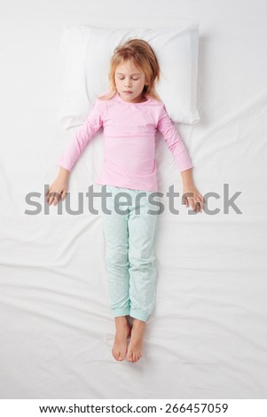 Top view photo of little girl sleeping on white bed. Quiet Soldier pose. Concept of sleeping poses - stock photo