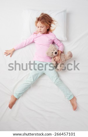 Top view photo of little girl sleeping on white bed with teddy bear. Quiet Freefaller pose. Concept of sleeping poses  - stock photo