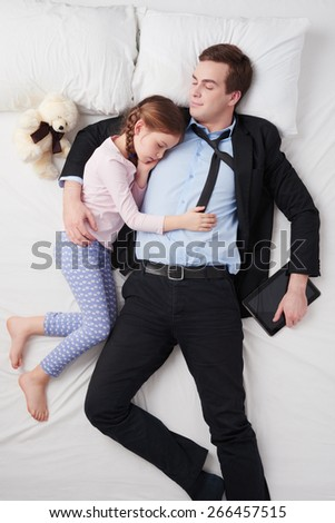 Top view photo of tired businessman wearing suit, and his little cute daughter. Father's arm is over daughter. They both sleeping on white bed. Man holding tablet computer - stock photo