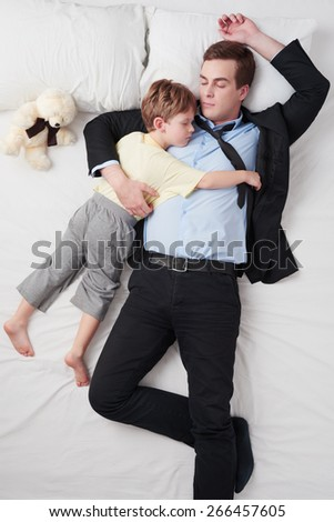 Top view photo of tired businessman wearing suit, and his little cute son. Father's arm is over son. They both sleeping on white bed - stock photo