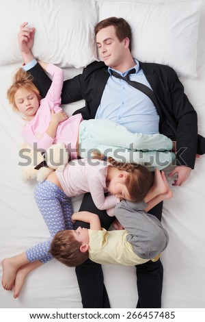 Top view photo of tired businessman wearing suit, and his three children. Children sleeping all over father - stock photo