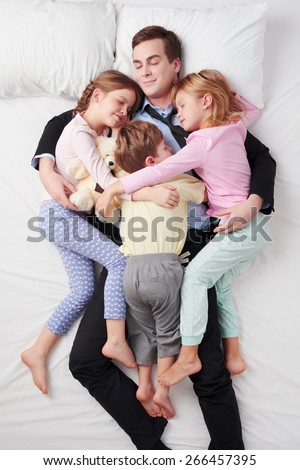 Top view photo of tired businessman wearing suit, and his three children. Father's arms are over daughters and son. They sleeping on white bed and hugging each other - stock photo