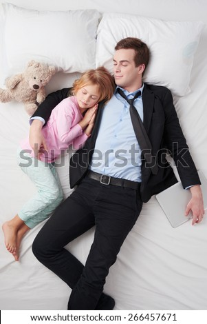 Top view photo of tired businessman with laptop wearing suit, and his little cute daughter. Father's arm is over daughter. They both sleeping on white bed - stock photo