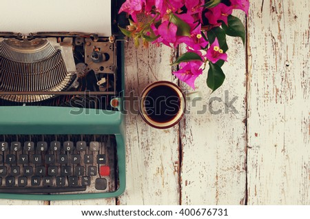 top view photo of vintage typewriter with blank page next to cup of coffee, on wooden table. retro filtered image  - stock photo