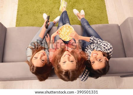Top view photo of women watching movie with popcorn - stock photo