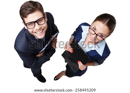 Top view photo of young business man and woman with glasses. They holding folders and looking at camera. Isolated on white background - stock photo