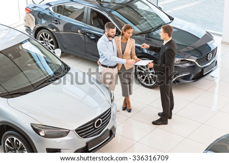 Top view photo of young male consultant and buyers signing contract for new car in auto show. Concept for car rental - stock photo