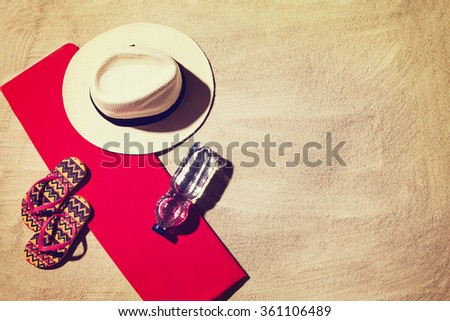Top view photograph of sandy beach with summer accessories and copy space around objects. Horizontal photo taken from above with visible sand texture. Vintage, retro effect processing. - stock photo