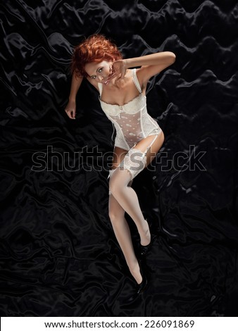 top view picture of sexy girl in white lace corset lying on the black silk with finger near the lips - stock photo