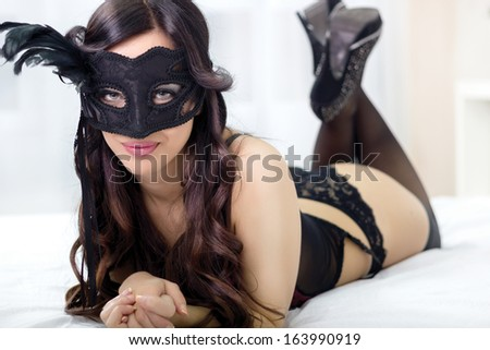 top view picture of sexy masked girl in black lingerie lying on bed - stock photo